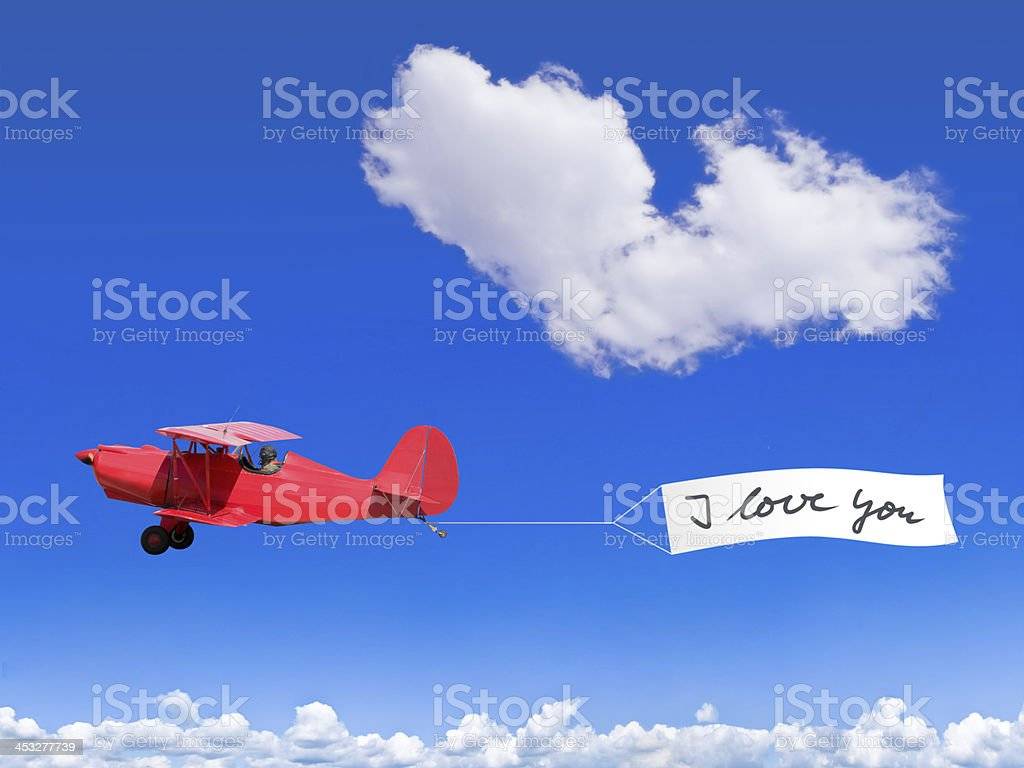 Red biplane with a banner and a cloud like a heart stock photo