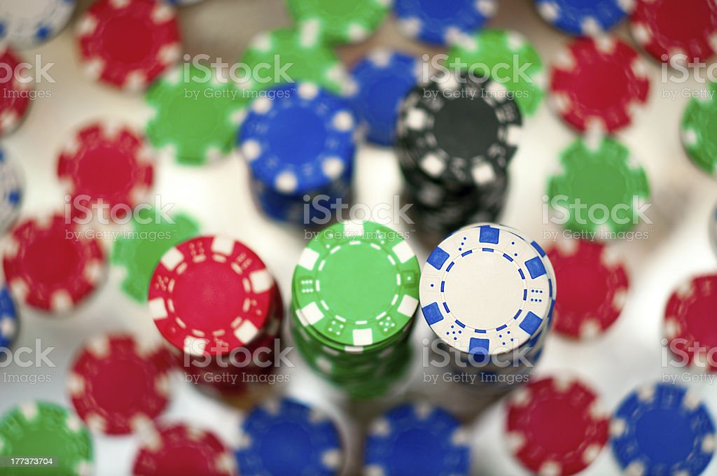 Red, blue, green and black casino tokens stock photo