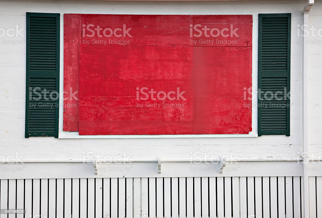 Red boarded window with green shutters on white stock photo