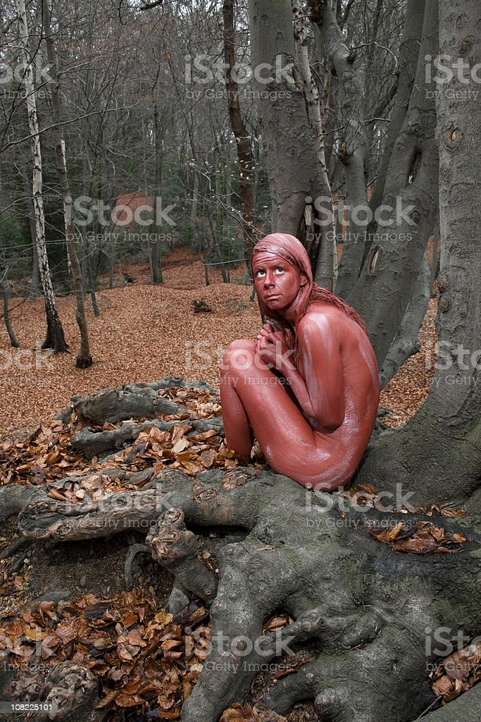 Red Body Painted Woman Sitting onTree in Autumn Woods royalty-free stock photo