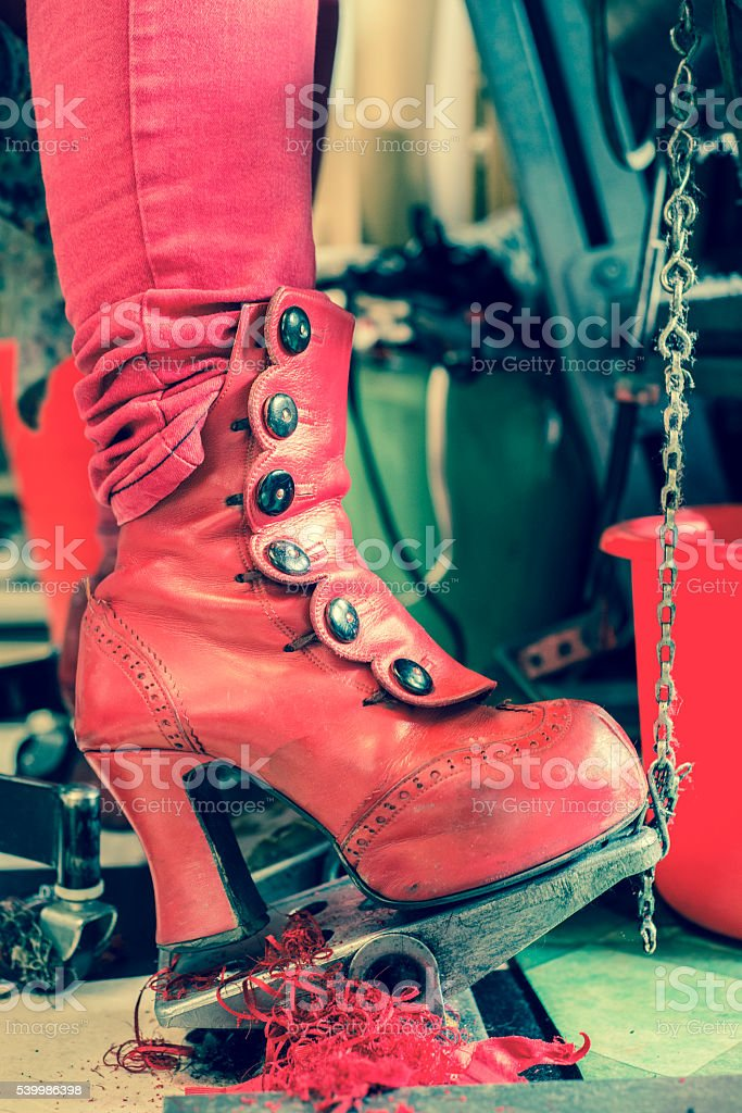 Red Boot on Sewing Machine Pedal stock photo