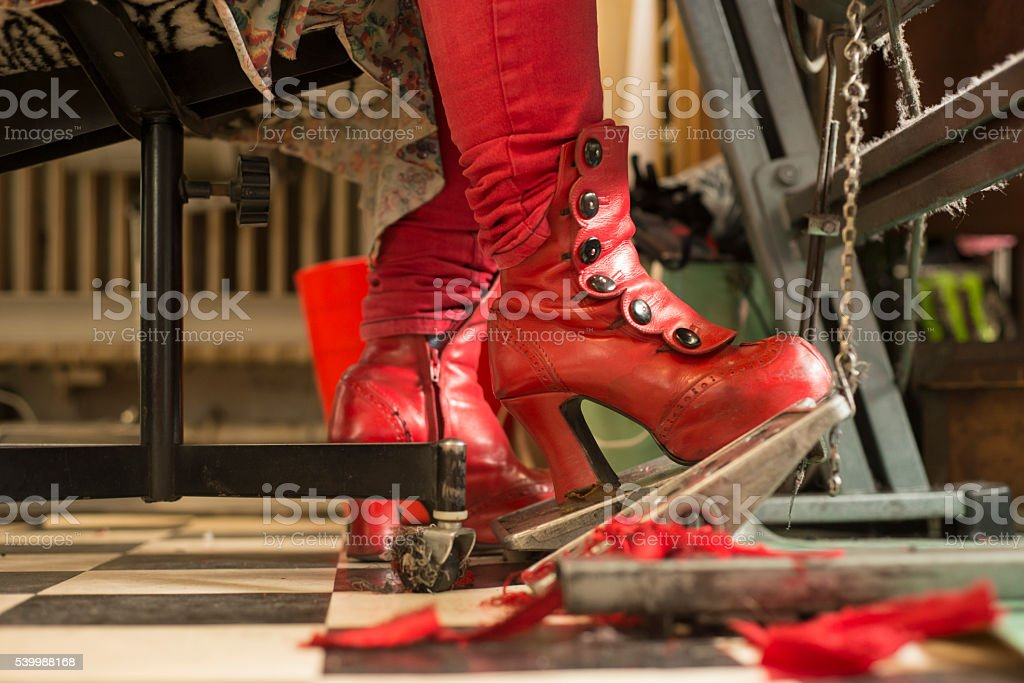 Red Boots on Sewing Machine Foot Controller stock photo