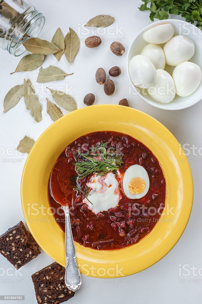 Red borscht soup in yellow plate from top stock photo