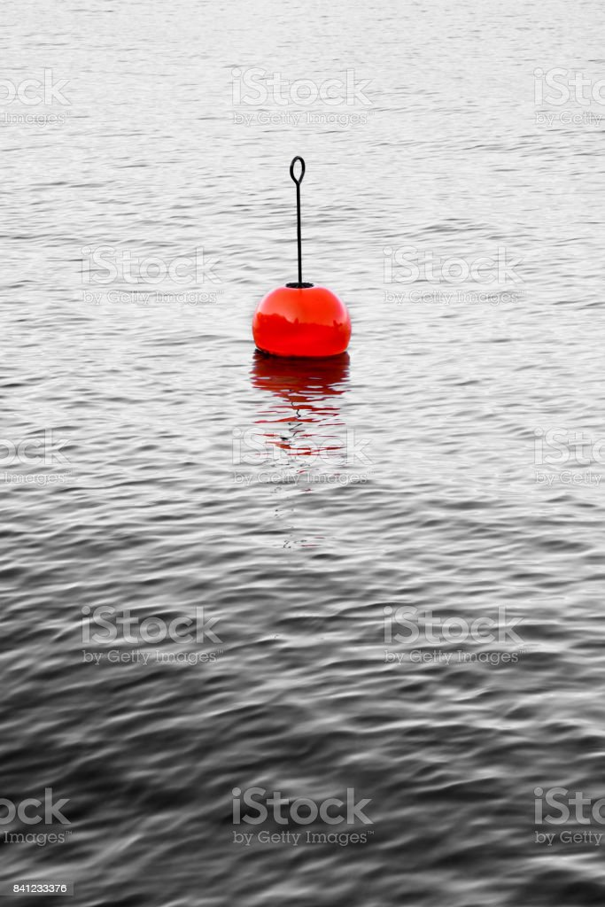 Red bouy on a calm lake - concept image with copy space stock photo