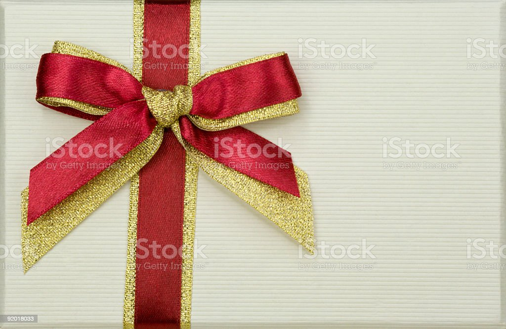Red bow on paper background, close-up royalty-free stock photo