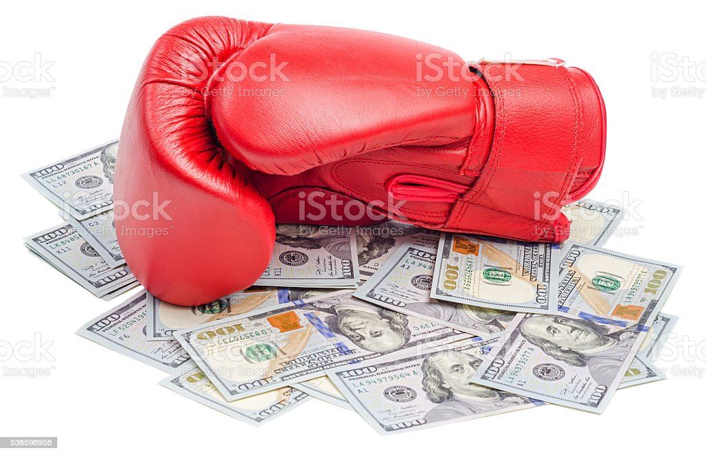 Red boxing glove on top of dollars bills isolated stock photo