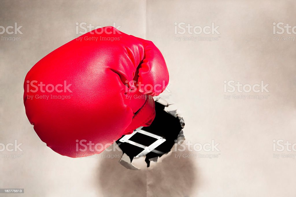 Red boxing glove punches through blank newspaper royalty-free stock photo