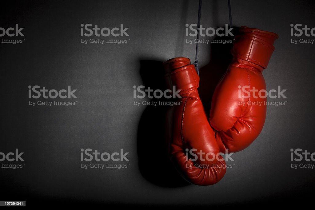 Red boxing gloves hanging against grey wall stock photo