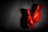 Red boxing gloves hanging against grey wall