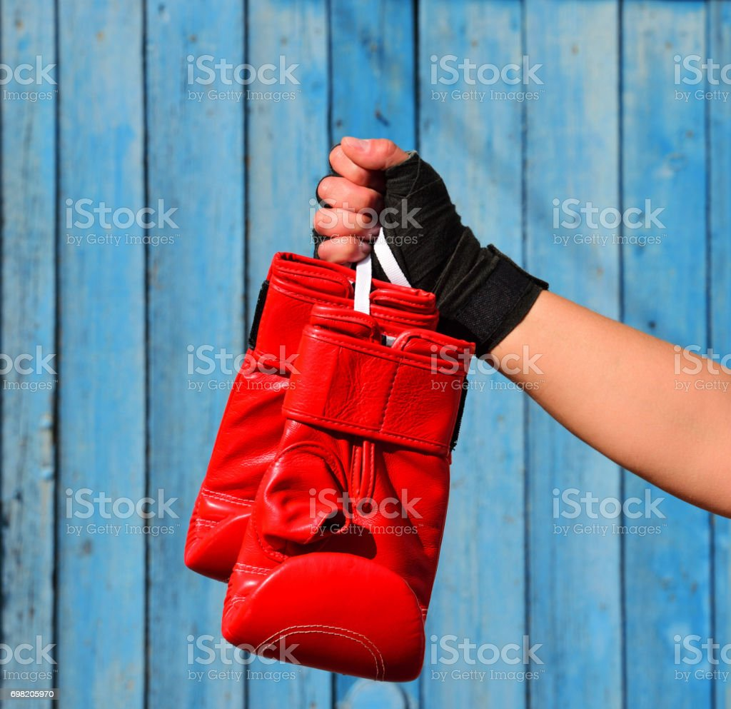 Red boxing gloves hanging on a rope in a woman's hand stock photo
