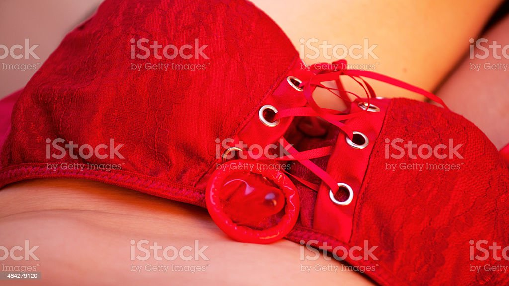 Red bra and condom on belly of transgender stock photo