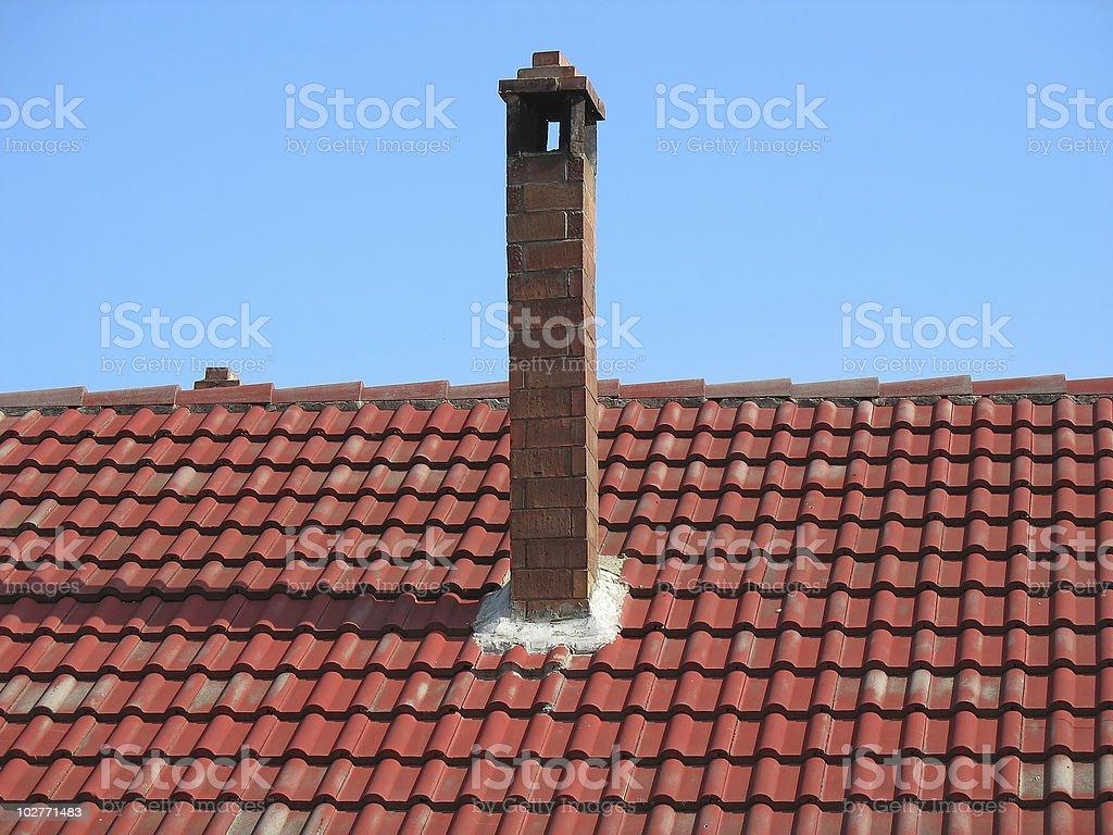 Chaminé de tijolo vermelho no telhado de Telha sobre céu azul foto de stock royalty-free
