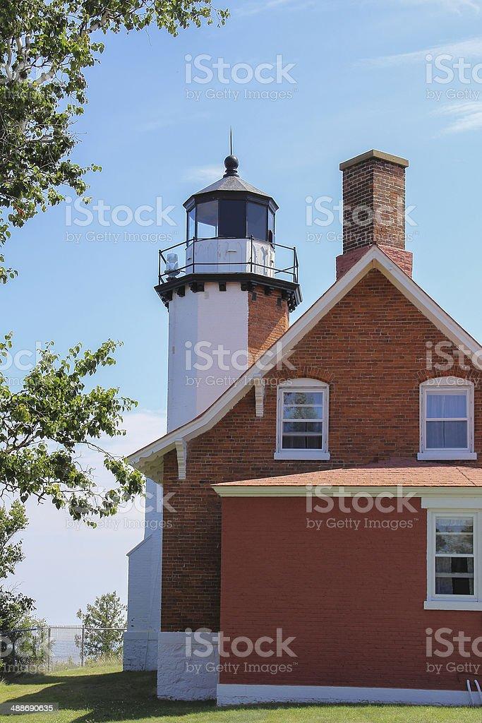 Red Brick Lighthouse and Light Blue Sky stock photo