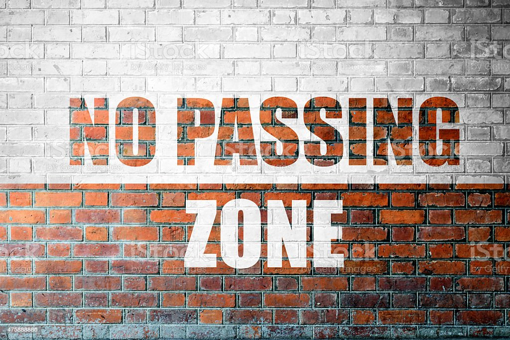 Red Brick wall texture with a word No Passing Zone stock photo