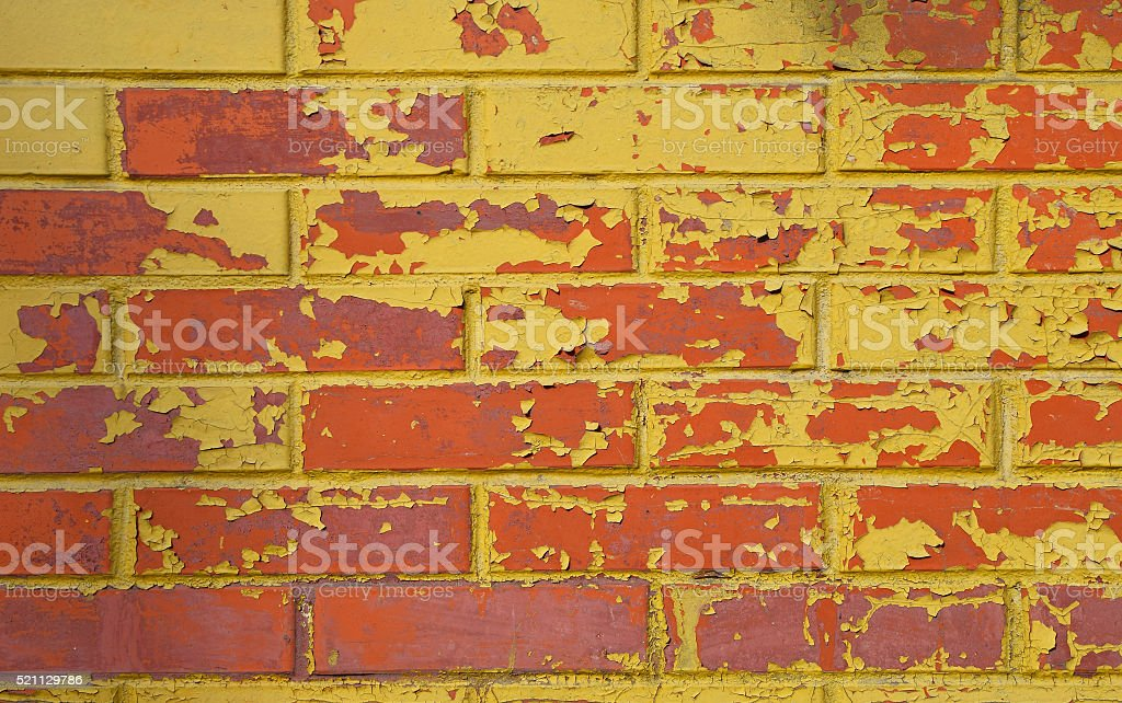 Red brick wall with flakes of yellow paint royalty-free stock photo