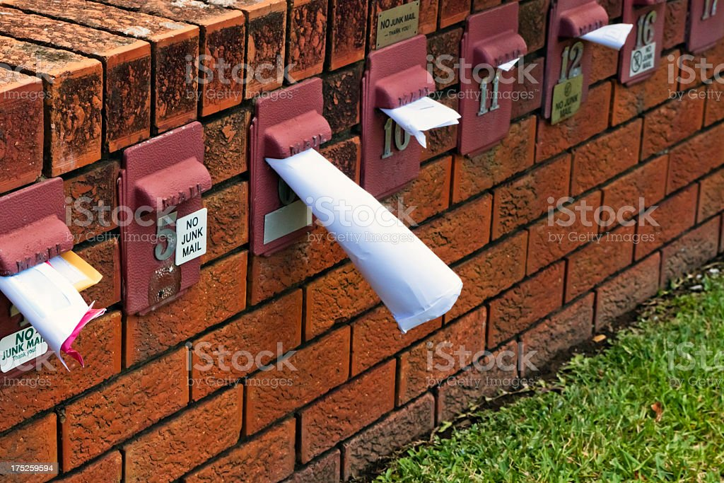 Red brick wall with letterboxes full of mail, copy space stock photo