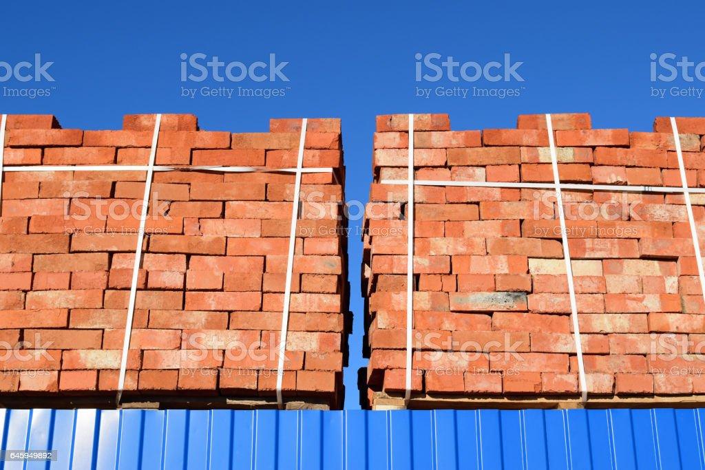 Red bricks stacked into cubes. Warehouse bricks. Storage brickworks products stock photo
