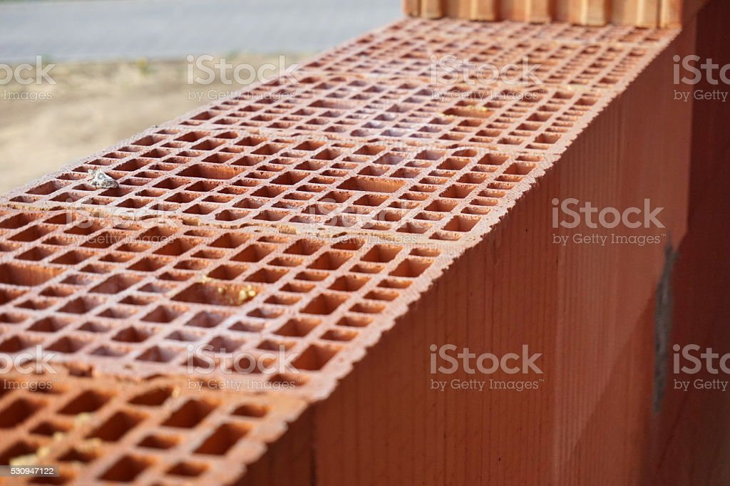 Red bricks with the holes in the shape of honeycomb stock photo