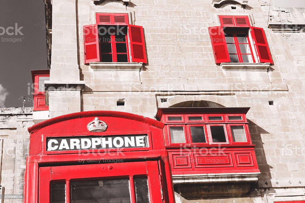 Red British telephone box and red shutter windows stock photo
