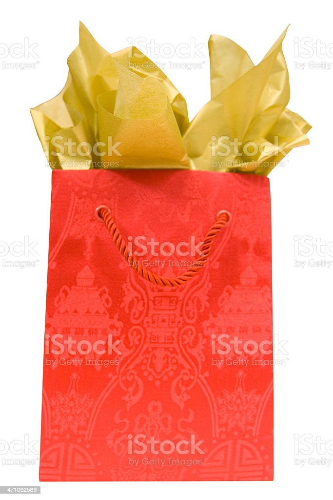 Red brocade gift bag with gold tissue stock photo