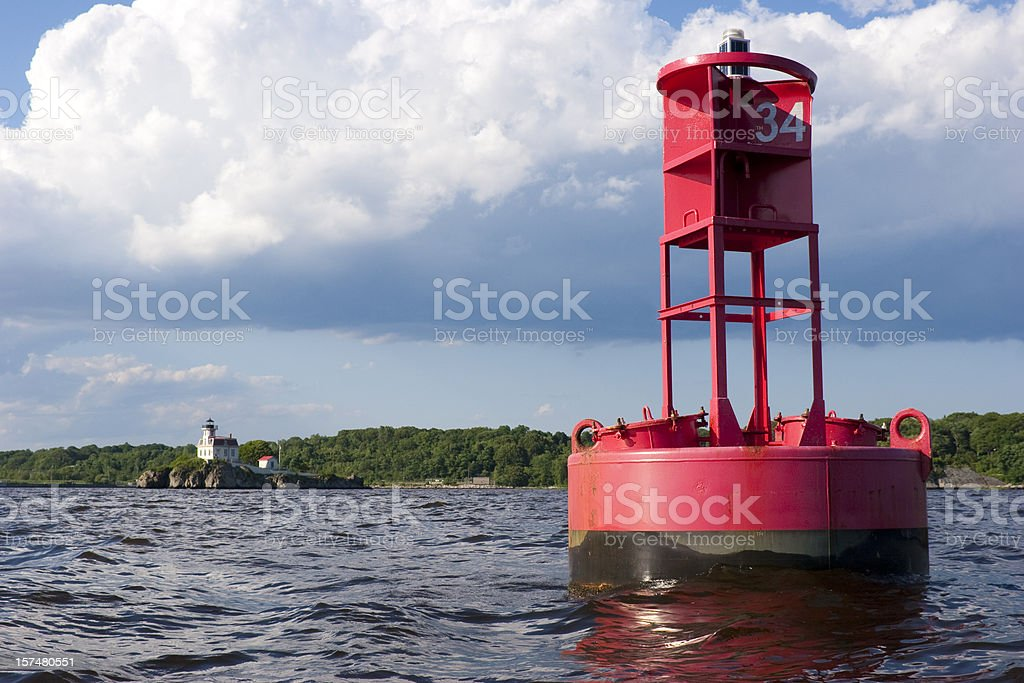 Red buoy and white lighthouse in Rhode Island stock photo