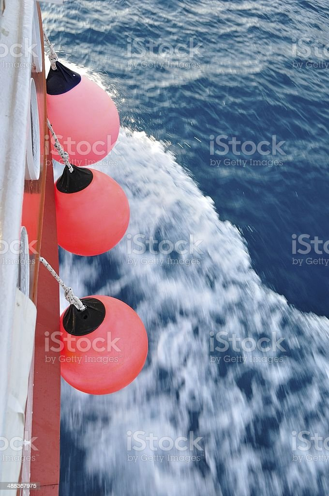 Red buoy on body of moving ship royalty-free stock photo