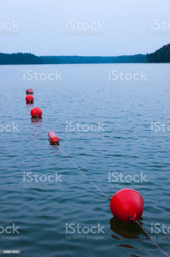 Red buoys, secure sweaming area on the lake at sunset. stock photo