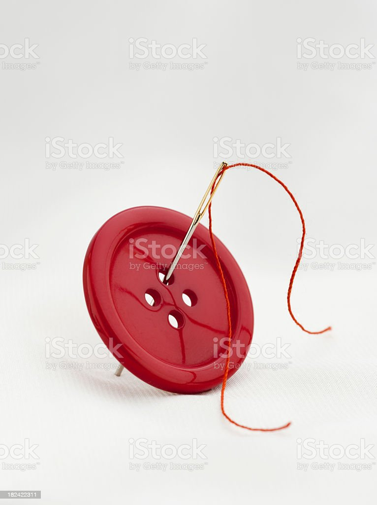 Red button with four thread holes and a needle with thread royalty-free stock photo