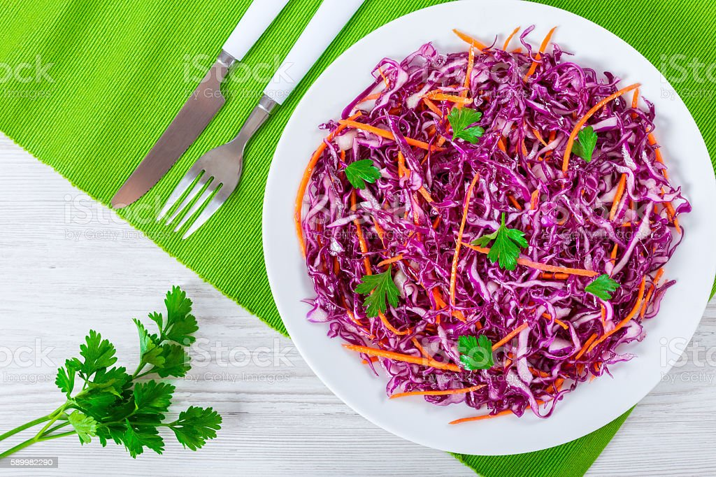 red cabbage salad with carrots and parsley on white dish stock photo