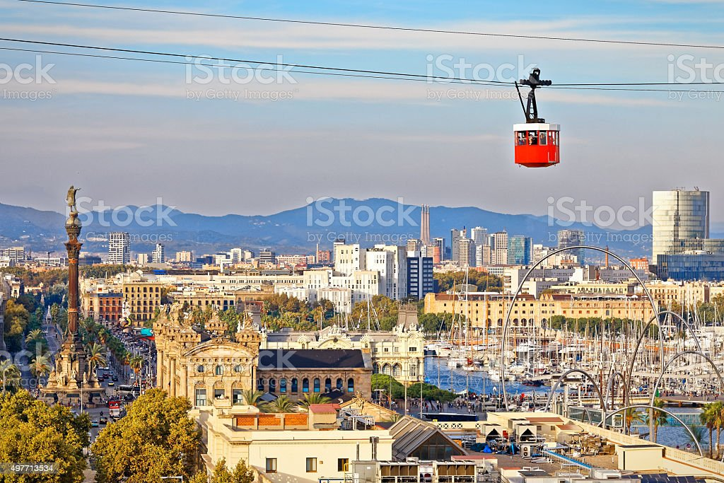 Red cabin of cableway stands out on Barcelona's port stock photo