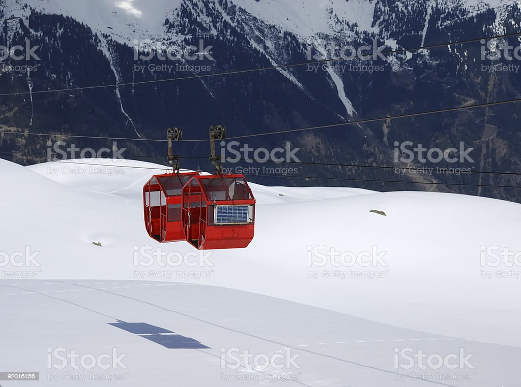 Red cabines of cable-way against black and white mountainside stock photo