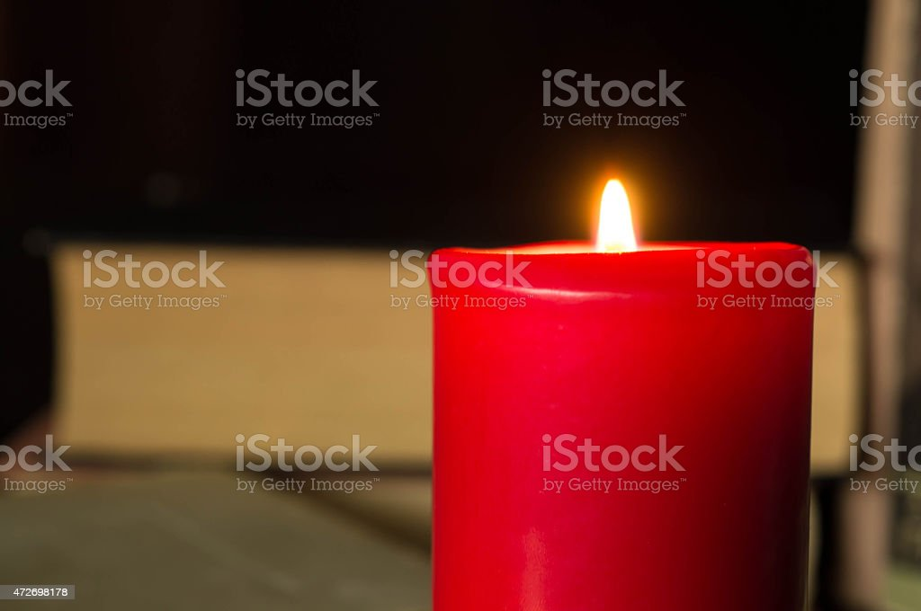 Red candle against several books stock photo