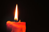 Red candle and lighting on black background