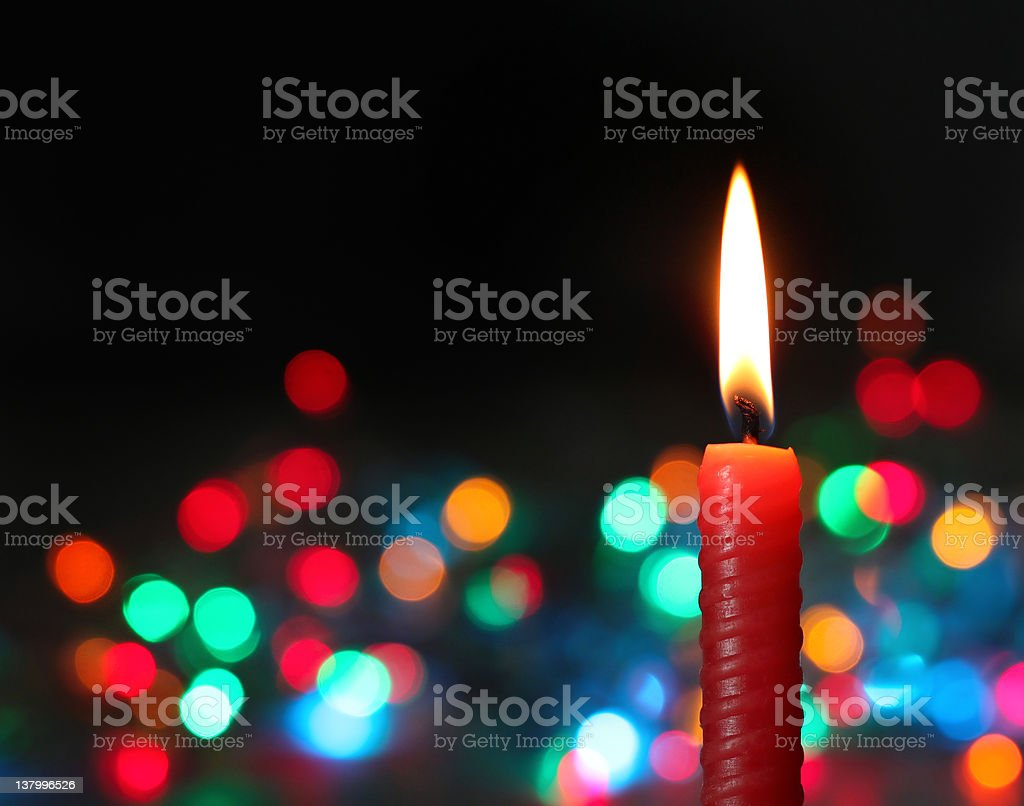 Red candle on dark background with lights royalty-free stock photo