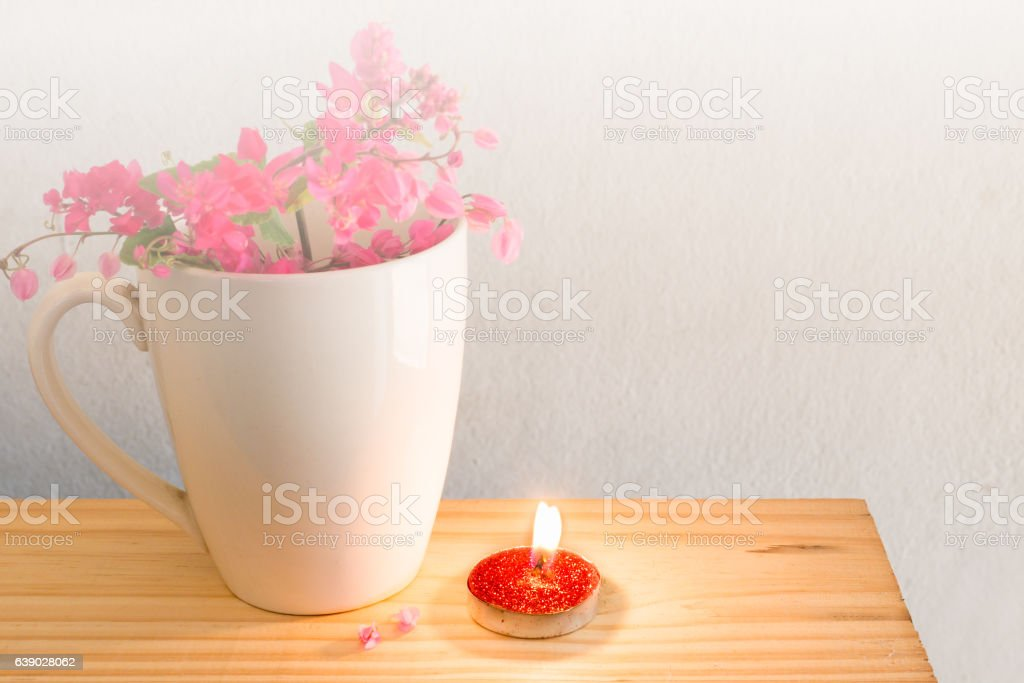 Red candle  white mug coffee and the Antigonon leptopus  flower. stock photo