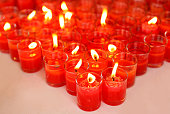 Red candles burning in glass