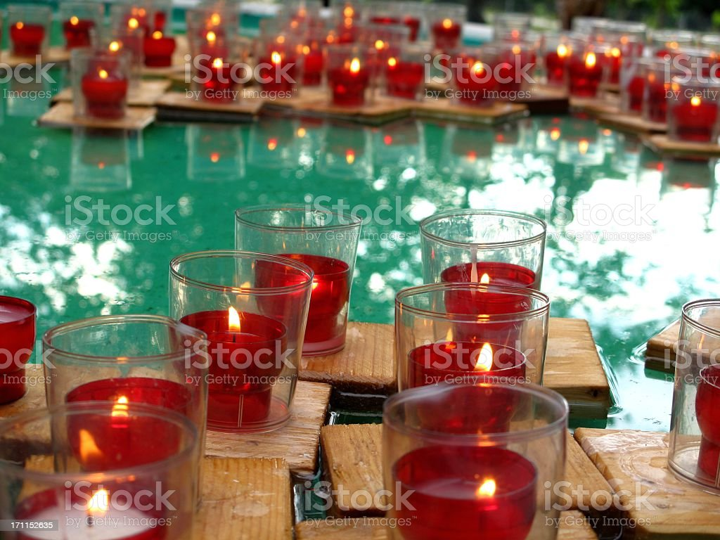 Red candles swimming in water stock photo
