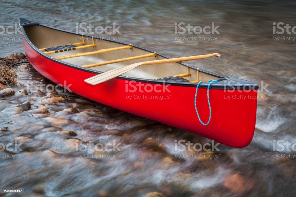 red canoe on a shallow rocky river stock photo