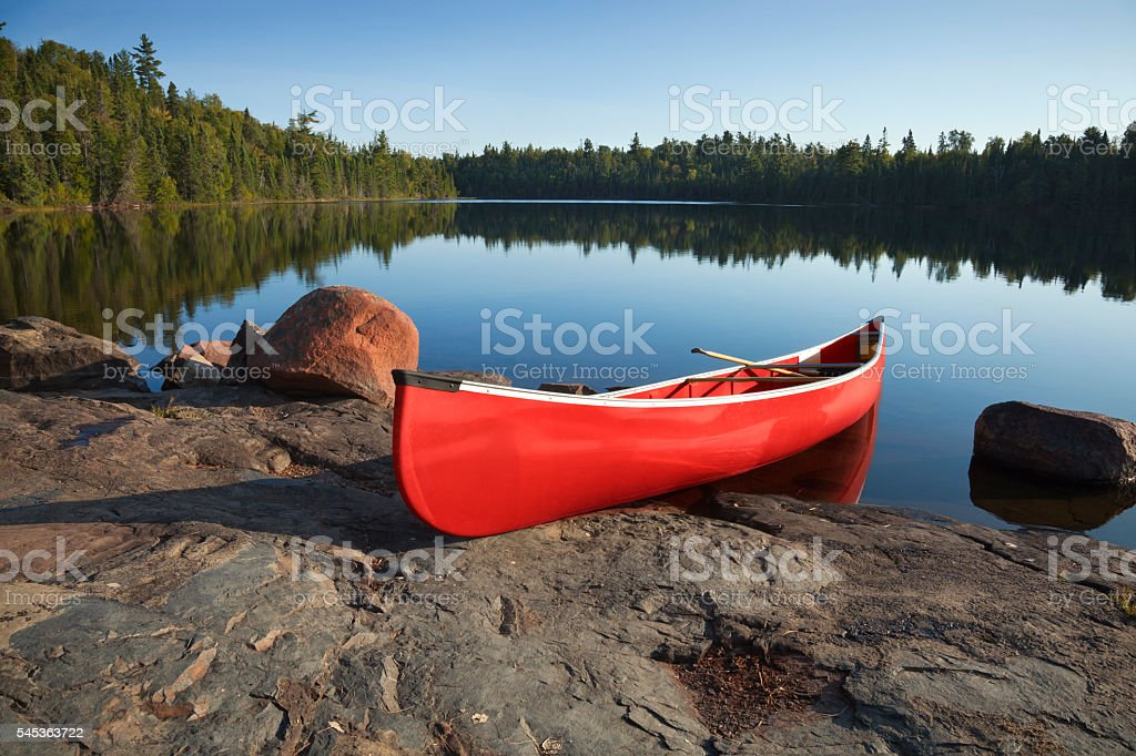 Red Canoe on Rocky Shore of Calm Northern Lake stock photo
