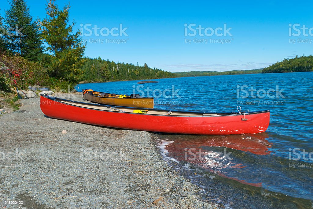 Red canoe on rocky shore  of Moose Lake BWCA stock photo
