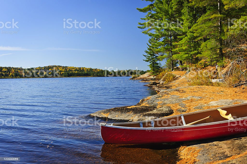 A red canoe on the shore of a mountain lake stock photo