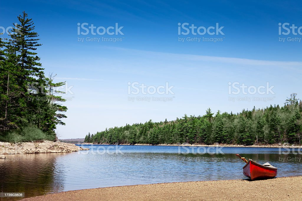 Red canoe stationed on a lake shore royalty-free stock photo