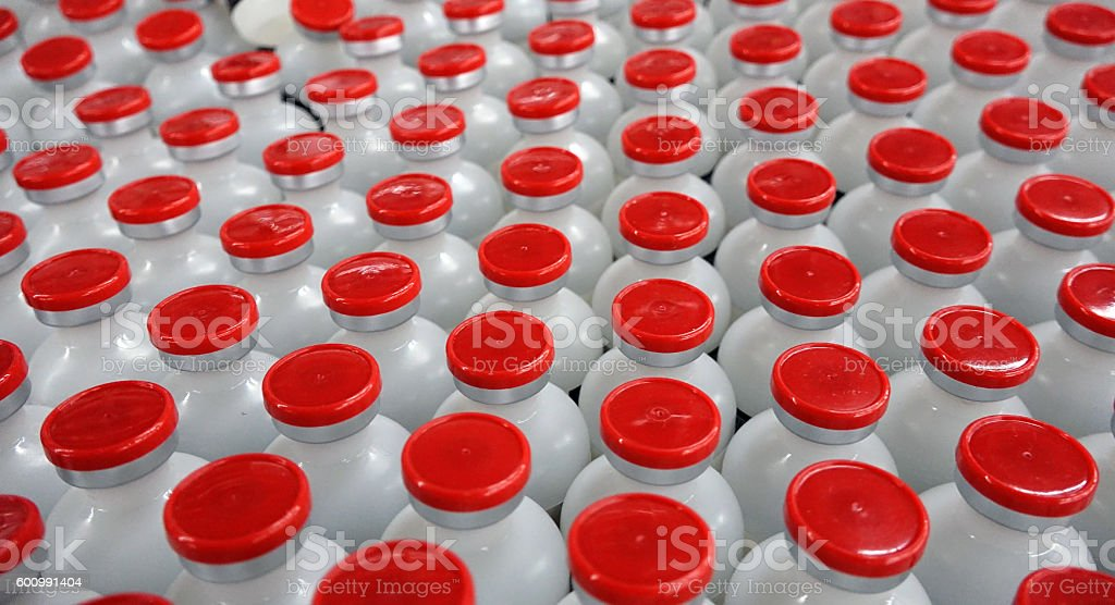 Shot of white bottles with red caps.