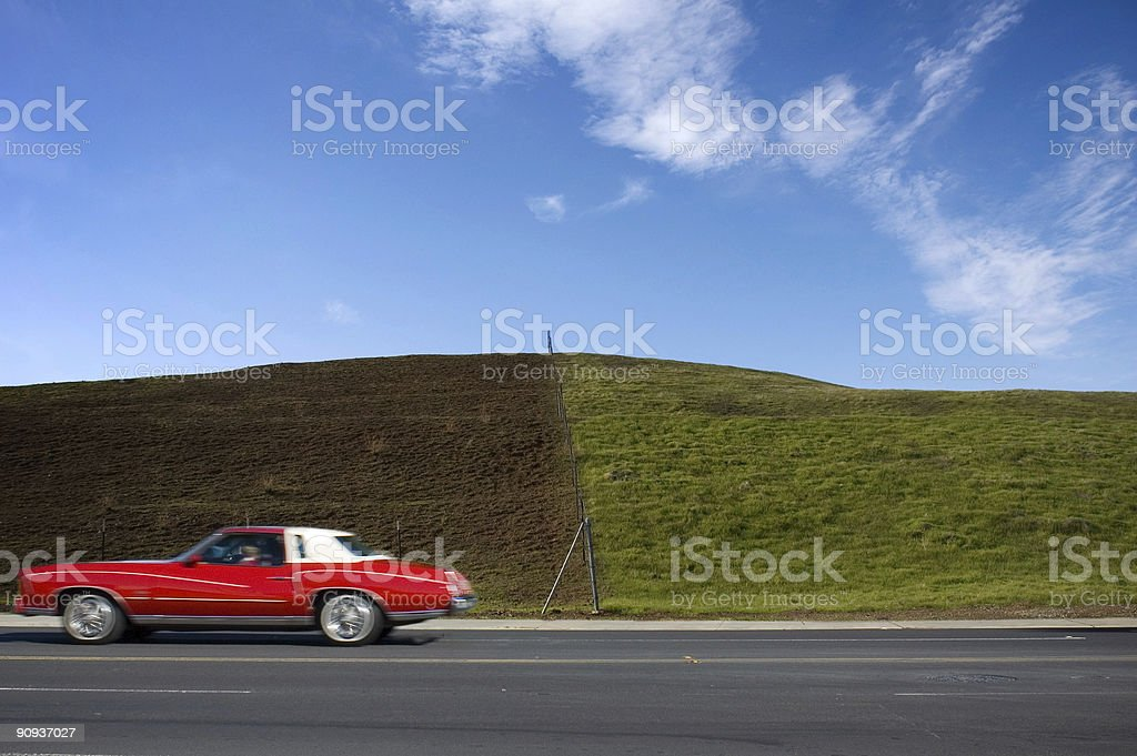 Red car and green hill stock photo