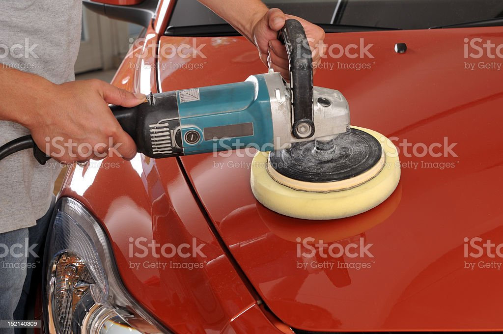 A red car being polished by a man stock photo