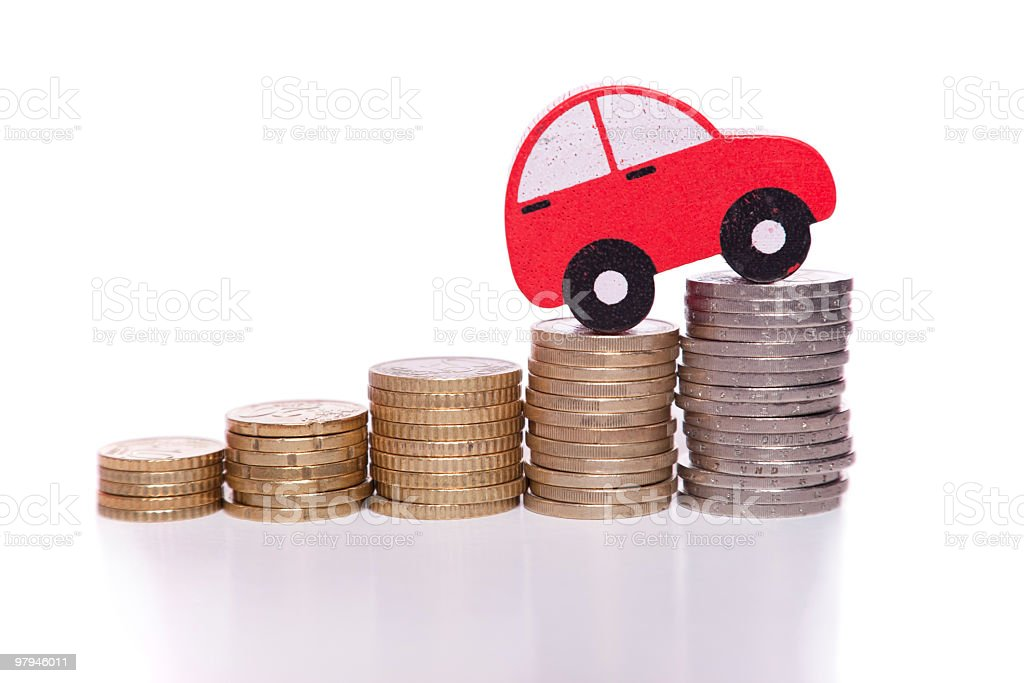 Red car cutout climbing stacks of coins stock photo