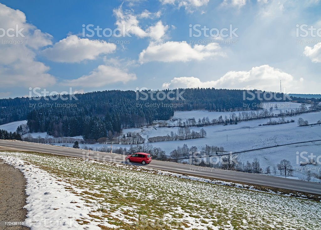 Red car driving along a mountain pass stock photo