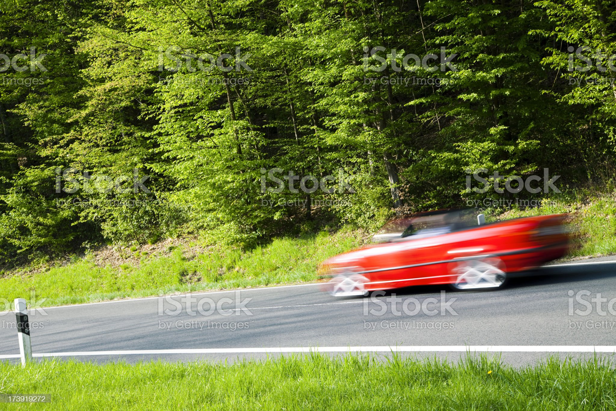 Red Car Driving Down Road Through Spring Forest, Blurred Motion royalty-free stock photo