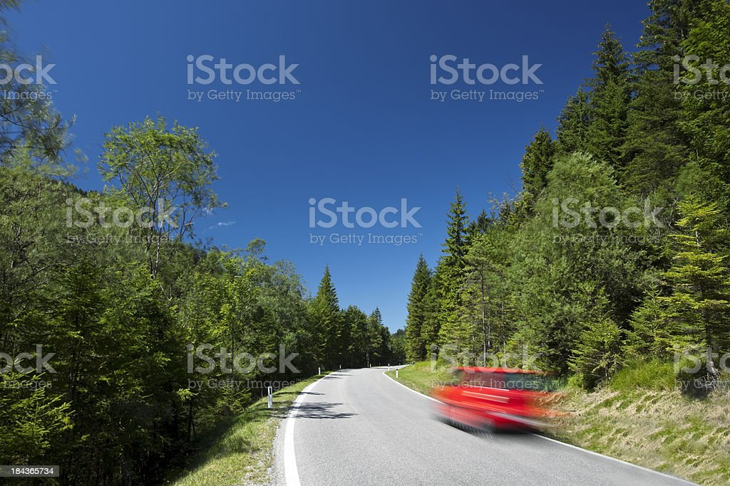 Red Car Driving on Country Road, Blurred Motion royalty-free stock photo