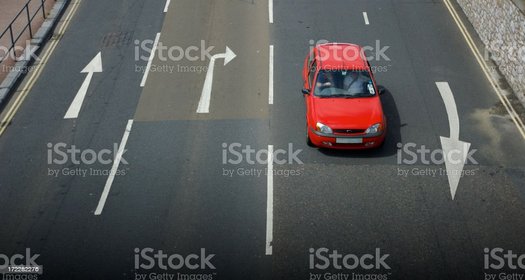 Red Car Driving on Road with Arrows from Above royalty-free stock photo